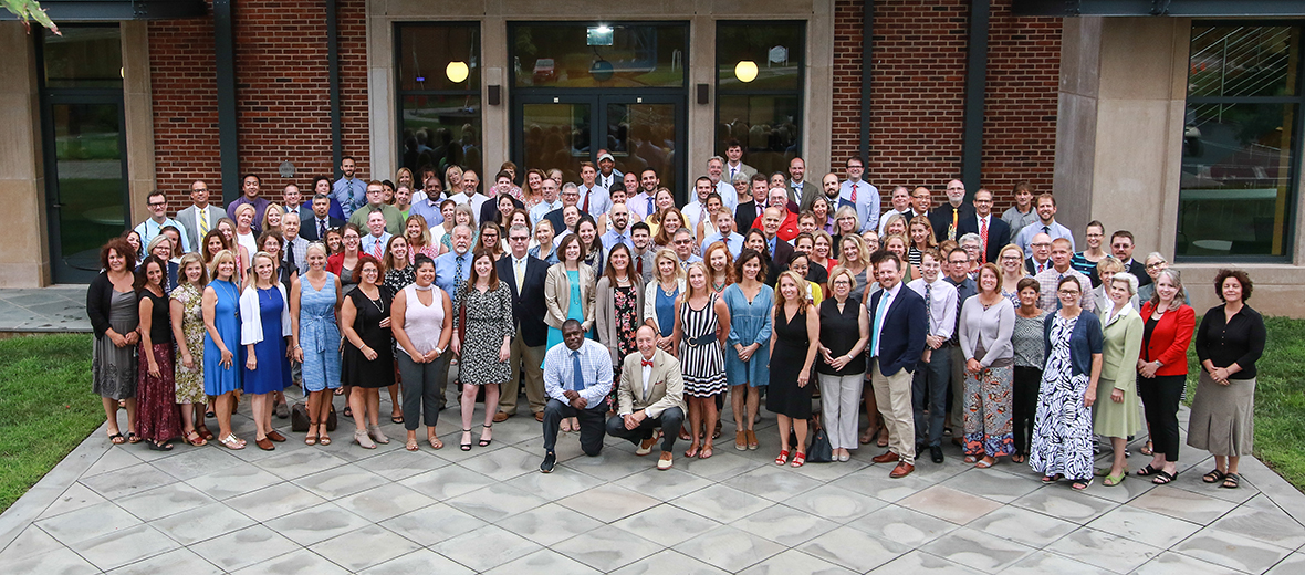 The entire faculty and staff standing in front of a building.