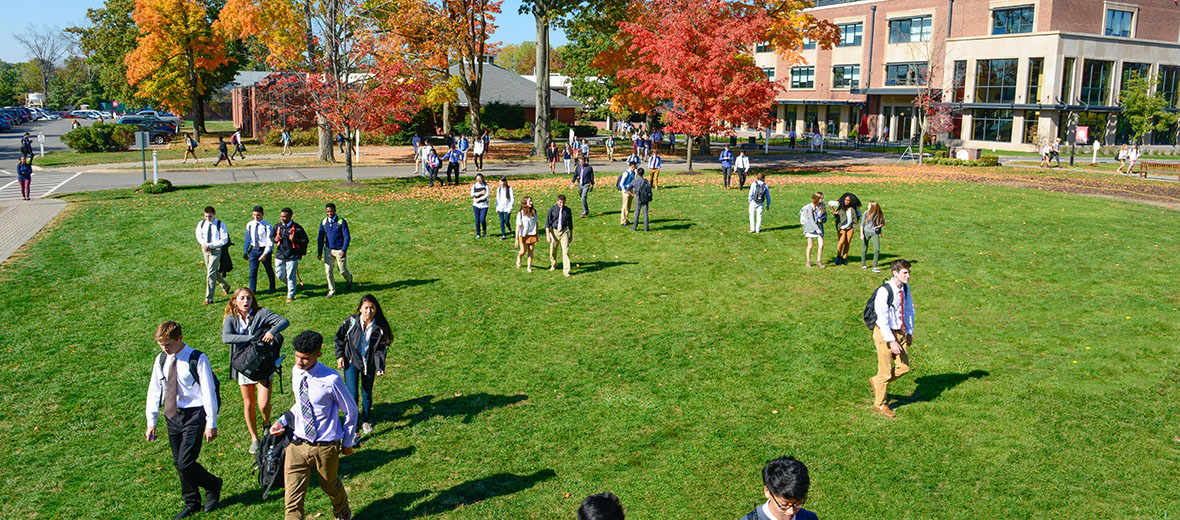 Students walking across a green lawn