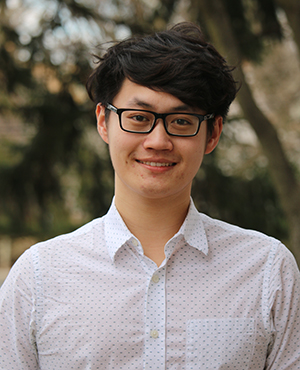 Male student outside smiling, wearing glasses.