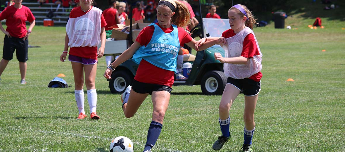 Girl soccer player kicking ball with others running.