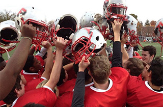 Football players holding their helmets together in a huddle.