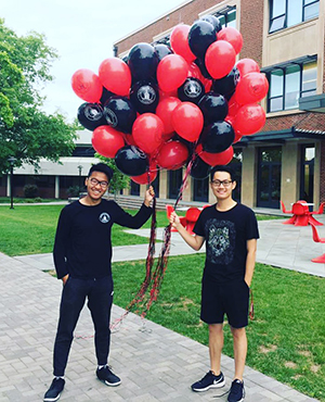 Two students holding red and black balloons on campus.