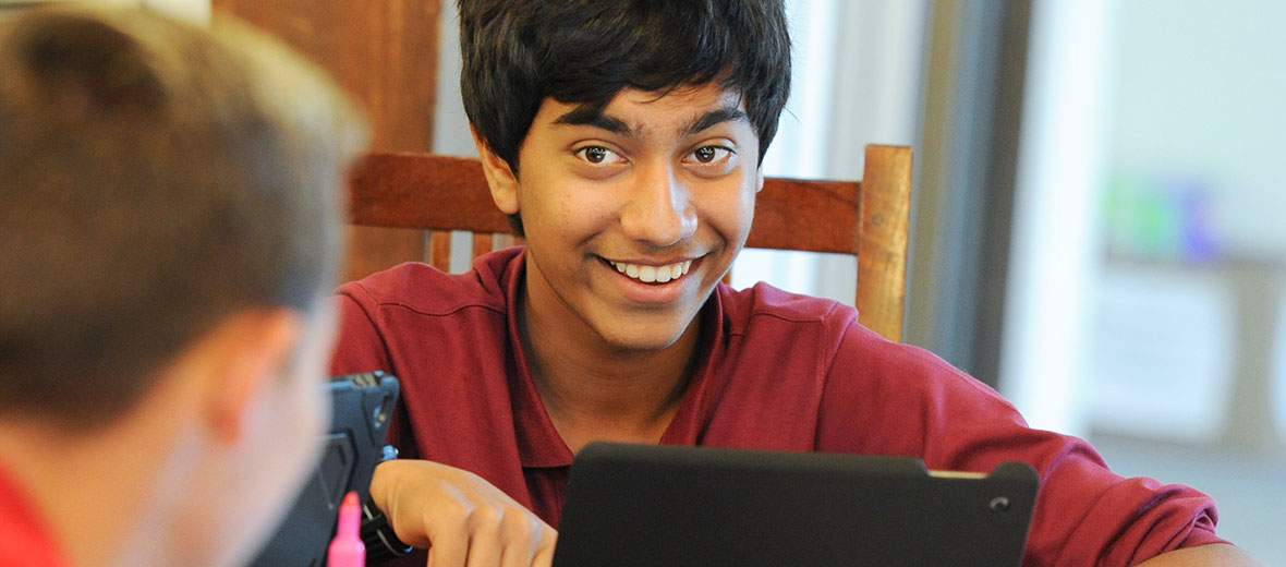 Male student looking over computer and smiling at another student.