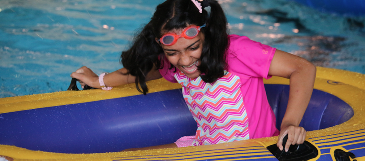 Female student in a raft floating in a pool