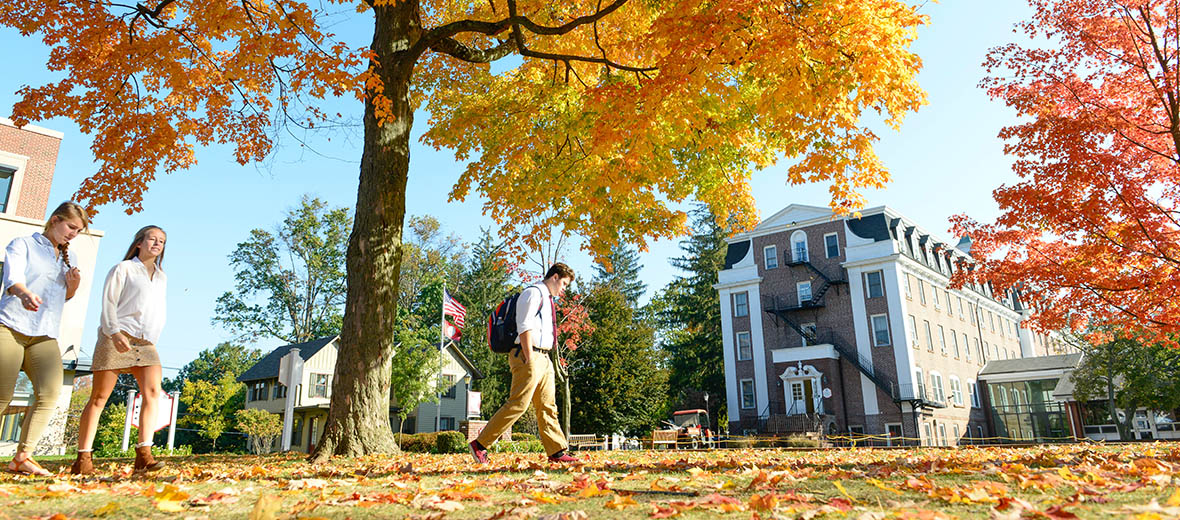 Students walking in fall, Old Main in the background.