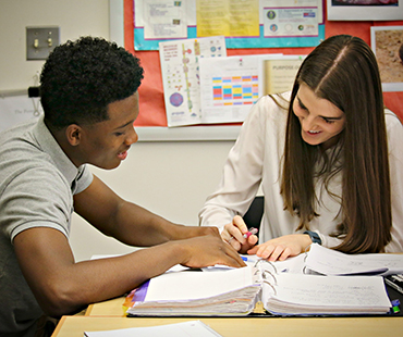 Two students at desk smiling and working