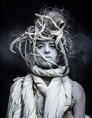 Photo of person wrapped in sheets or twigs.