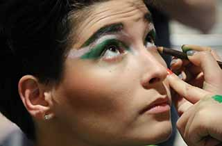 A female student getting her make-up applied for a drama performance.