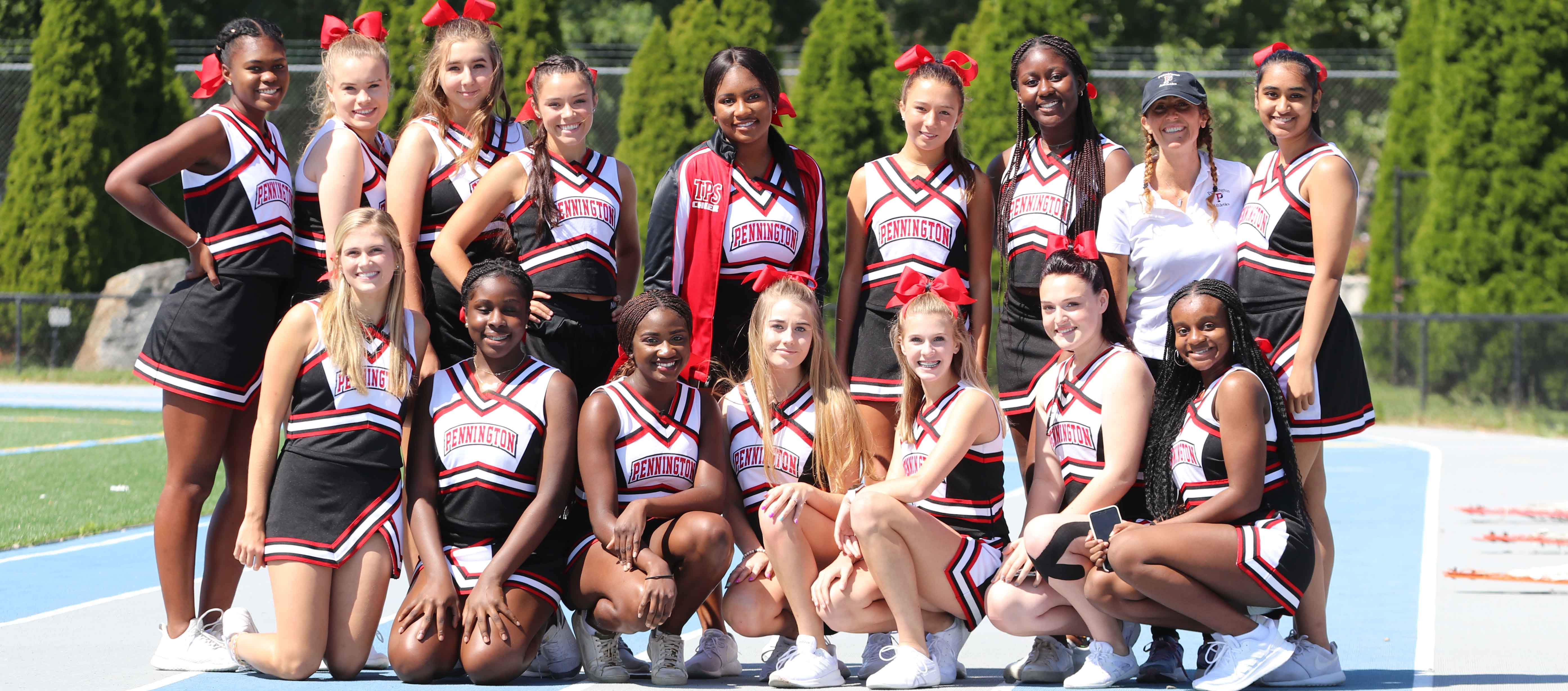 The cheerleading team poses outside
