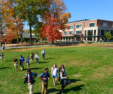 Green lawn with Yen building in back and students walking on lawn