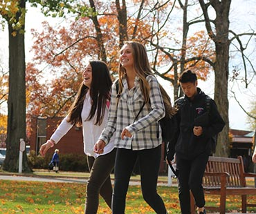 Students smiling walking across campus