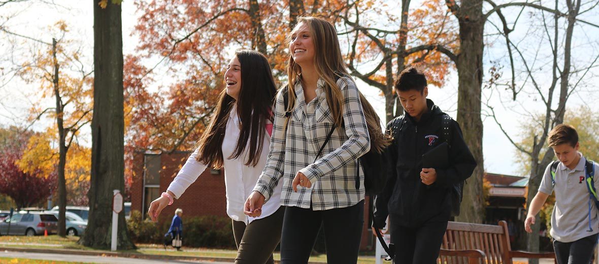 Students walking across campus laughing together